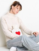 young woman with hot water bottle heart_style