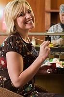 Woman in sushi restaurant