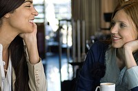 Two female friends having coffee and chatting in cafe