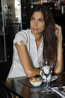 Brunette woman sitting in cafe, daydreaming