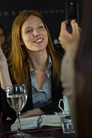 Woman posing for photo taken with cell phone in cafe