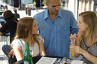 Man talking to two young women at outdoor cafe