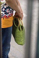 Woman holding handbag, cropped view