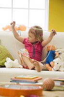 Little girl sitting on sofa with toys, playing with costume jewelry