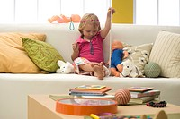 Little girl playing with toys and costume jewelry on sofa