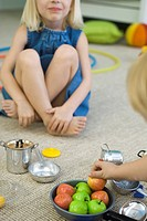 Children sitting on floor, playing with pots and pans, cropped