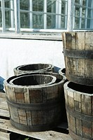 Barrel planters stacked by wall