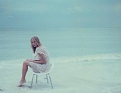 Young female sitting in chair on beach, looking at camera, full length
