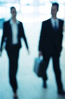 Businessman and businesswoman walking side by side, front view, defocused