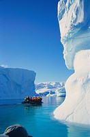 Tourists in inflatable cruising past icebergs, Antarctica