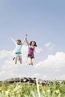 two girls jumping up in the air