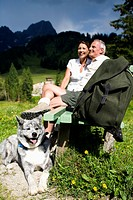 mature couple with dog sitting on bench in the mountains
