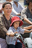 Cambodian mom and daughter ride motorbike in heavy traffic, Phnom Penh, Cambodia No model releases available