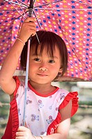 Young Lao girl protects herself from the sun with an umbrella, Mekong region, Laos No model release available