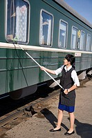 Railway stewardess on Mongolian train cleans windows at stop between Beijing and Ulaan Baatar, Mongolia No release available