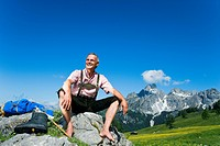mature man sitting barefoot on rock in the mountains