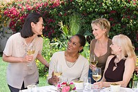 Female friends drinking wine at outdoor table
