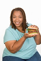 Portrait of Mid_adult overweight woman holding big cheeseburger and smiling