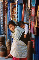 Woman and baby, cloth shopkeeper in temple square, Bodhnath, Kathmandu, Nepal