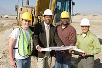 Surveyor and construction workers on site portrait