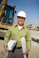 Surveyor holding blueprints on construction site portrait