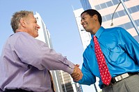 Two businessmen shaking hands outdoors