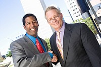 Portrait of two businessmen shaking hands outdoors