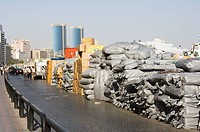 Goods stacked on the dockside of the Dhow Wharfage awaiting transportation by dhow to ports throughout the Middle East, India and Asia, Dubai Creek, D...