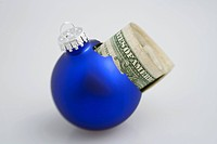 Closeup of one blue Christmas tree bulb ornament broken with dollar bills inside peeking out on white background studio portrait