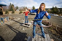 Two young women hula_hoop on top of picnic tables in Homer, Alaska