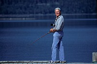 Mature Man Fishing In Lake, Smiling