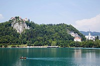 Traditional wooden pletnja rowing boat to ferry tourists to St. Mary´s Church of Assumption on the islet beyond, Lake Bled, Slovenia, Europe