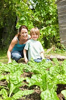 Boy gardening with mother portrait