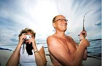 Ett Medelålderspar Sitter I En Båt. Mannen Är Glad Och Fiskar Och Kvinnan Fotograferar., Mature Couple In Boat Women Photographing