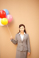 A businesswoman holding balloons