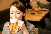 Woman drinking beer in the Japanese_style pub