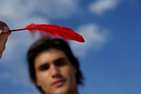 Man holding a red feather in his hand