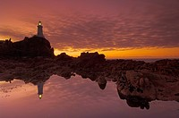 Dramatic sunset and low tide, Corbiere lighthouse, St. Ouens, Jersey, Channel Islands, United Kingdom, Europe