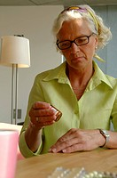 Senior woman holding a glass with pharmaceuticals in one hand while looking unhappy, close_up