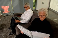 Senior man using a laptop while woman reading a book