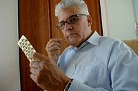 Senior man about to take a pill from a package, close_up