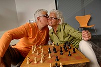 Senior man kissing a senior woman on her cheek, chessboard in front of them