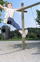 Blonde boy jumping from a Rubber Tire_Swing _ Playground _ Fun _ Courage _ Freedom