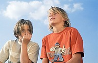Two Boys sitting next to Each Other under the blue Sky _ Friendship _ Boredom _ Youth