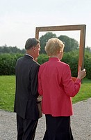 Someone taking a Picture of an old married Couple through a Frame _ Festivity _ Family Party _ Garden