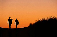 Silhouette of two people walking with surfboards on the beach
