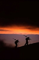 Silhouette of two skiers hiking at sunset after a storm while skiing, Mt Hood, Mt Hood National Park, Oregon, USA