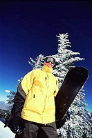 Low angle view of a man holding a snowboard, Diamond Peak, Nevada, USA