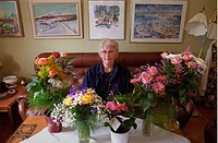 Mamma Fyller 75 År, Flowervases On Table And Woman Sitting On Sofa Near It, Elevated View