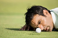 Man looking at golf ball